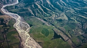 Ariel view of glacial fed braided river, centre pivot irrigation on floodplains and sheep grazed hill country. The bold patterns of fossil fue powered landuses overlaying the crisp land forms of geologically young New Zealand  South Island  landscapes
